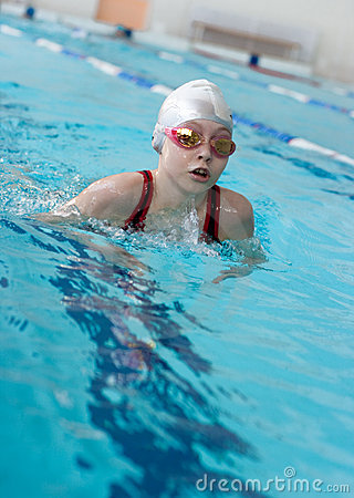 Girl swimming breaststroke in pool
