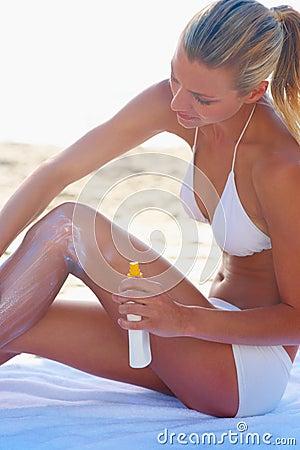 Girl in swimsuit applying sun cream lotion to skin