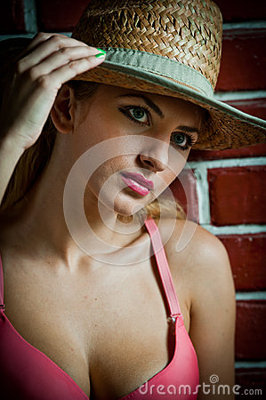 Girl in swimsuit posing provocatively in front of a brick wall