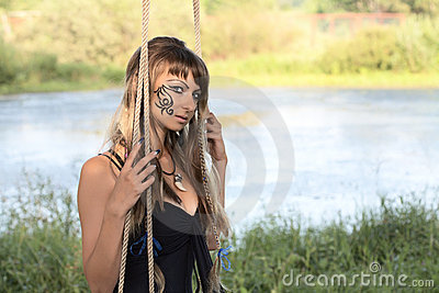 Girl on  swing against a pond