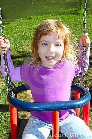 Girl swinging on swing happy in meadow grass park