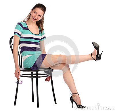 Girl take leg up sitting on stool.