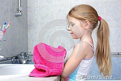 Girl taken towel after washing in bathroom
