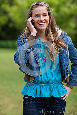 Girl talking on the phone while standing in a pa
