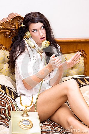 Girl talking on telephone and making manicure