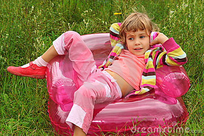 Girl talks by toy phone in inflatable armchair