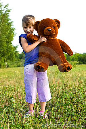 Girl with teddy bear in a meadow