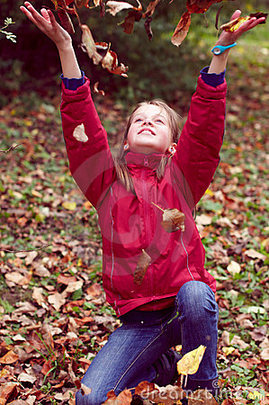 Girl teen playing with autumn leaves up in the air