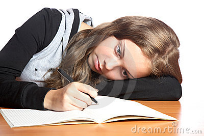The girl-teenager looks in  writing-book