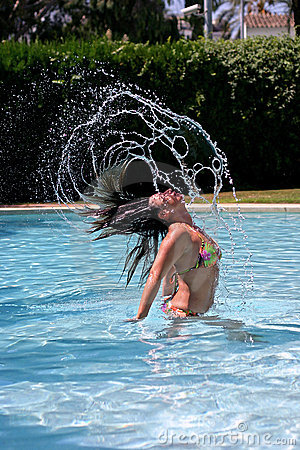 Girl throwing hair back fast in sunny, blue swimming pool