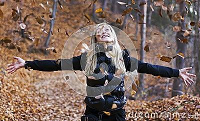 Girl throwing leaves in air
