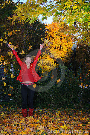 The girl throws autumn leaves upwards