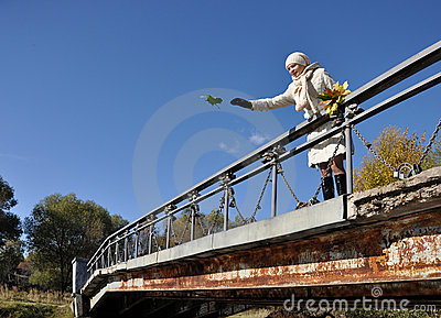 Girl throws maple sheet to the water from bridge