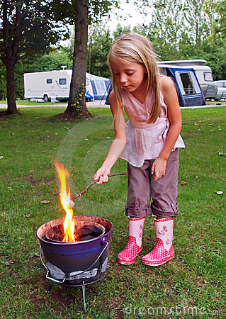 Girl toasting marshmallows on Camp Fire