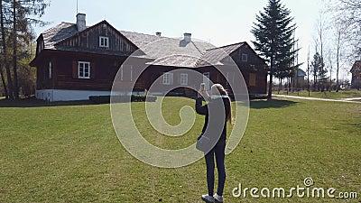 Girl Tourist macht Fotos von Holzhaus in einem alten europäischen Dorf