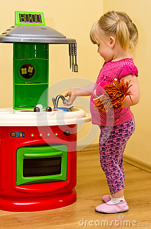 Girl and toy kitchen