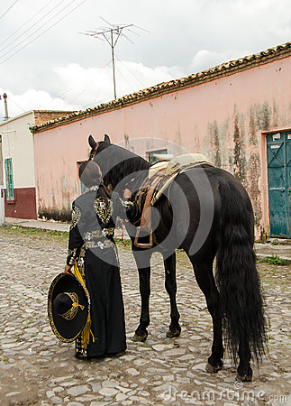 Girl in traditional Mexican outfit and black horse