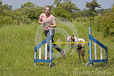 Girl training her dog to jump