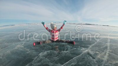 Girl is training practice yoga in winter. Children is do stretching and meditation on ice in nature. Kid practices yoga. Doing twine with cracks ice. Child do stock footage