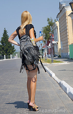The girl-traveller with a backpack in the street