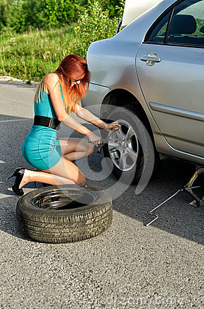 Girl is trying to change a tire