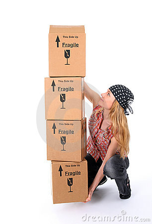 Girl trying to lift a stack of cardboard boxes