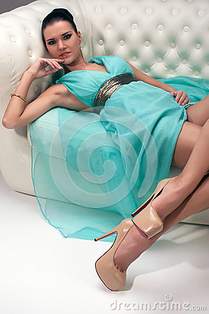 Girl in a turquoise dress on sofa