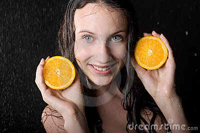 Girl with two halfs of orange in water studio