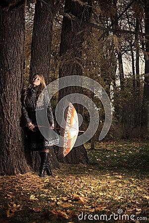 Girl with umbrella in autumn park