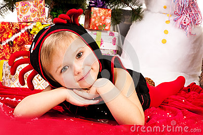 A girl under the Christmas tree with gifts