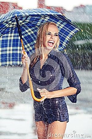 Girl under umbrella watching the rain