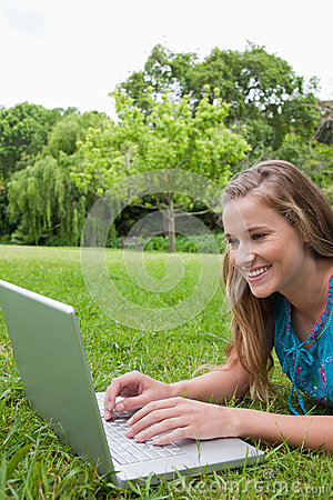 Girl using her laptop in a park while lying down