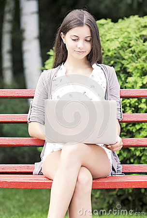 Girl using a laptop on a bench