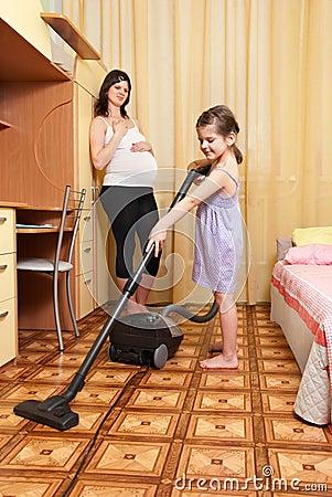 The girl vacuums a floor