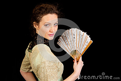 Girl in Victorian dress with fan in profile