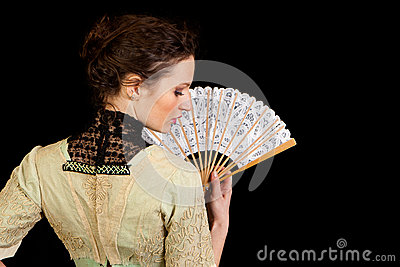 Girl in Victorian dress with fan seen from the back