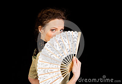 Girl in Victorian dress hinding behind a fan