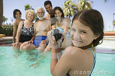Girl With Video Camera Recording Family In Swimming Pool