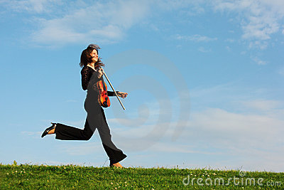 Girl with violin runs against sky, side view