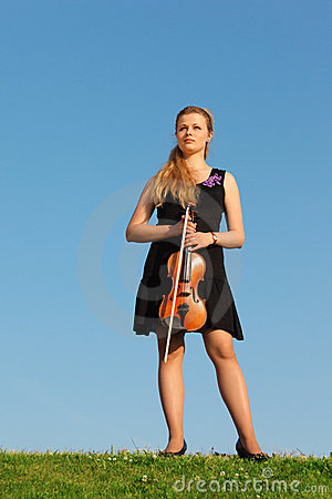 Girl with violin stands on grass against  sky