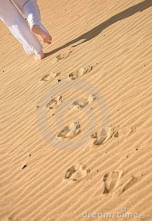 Girl waking on the beach - footprints