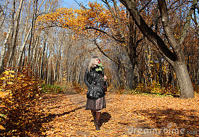 Girl walking in autumn park alley