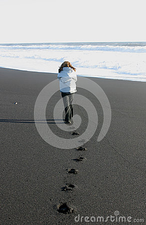 Girl walking away on a beach in Iceland Editorial Photography