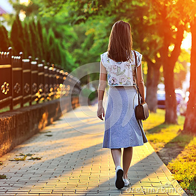 Free Girl Walking Away Through Green Alley At The Sunset Stock Photography - 42344612