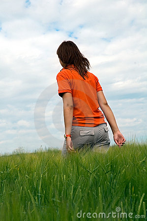 Girl walking in field of green wheat