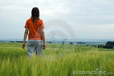 Girl walking in field overlooking valley