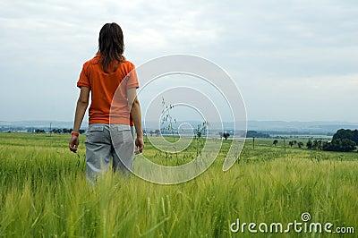 Girl walking in field overlooking valley