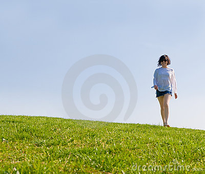 Girl walking on the green hill