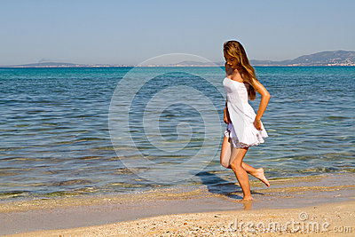 Girl walking on a white sandy beach