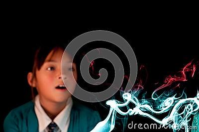 Girl watches colorful smoke.